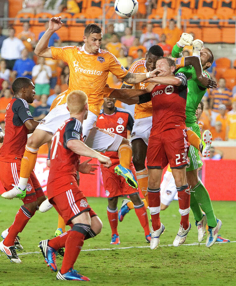 The Houston Dynamo collide with Toronto FC as the Dynamo attempt to score during the second half of a soccer game at BBVA Compass Stadium Wednesday, June 20, 2012, in Houston. The game ended in a 3-3 draw. Photo: Cody Duty, Houston Chronicle / © 2011 Houston Chronicle