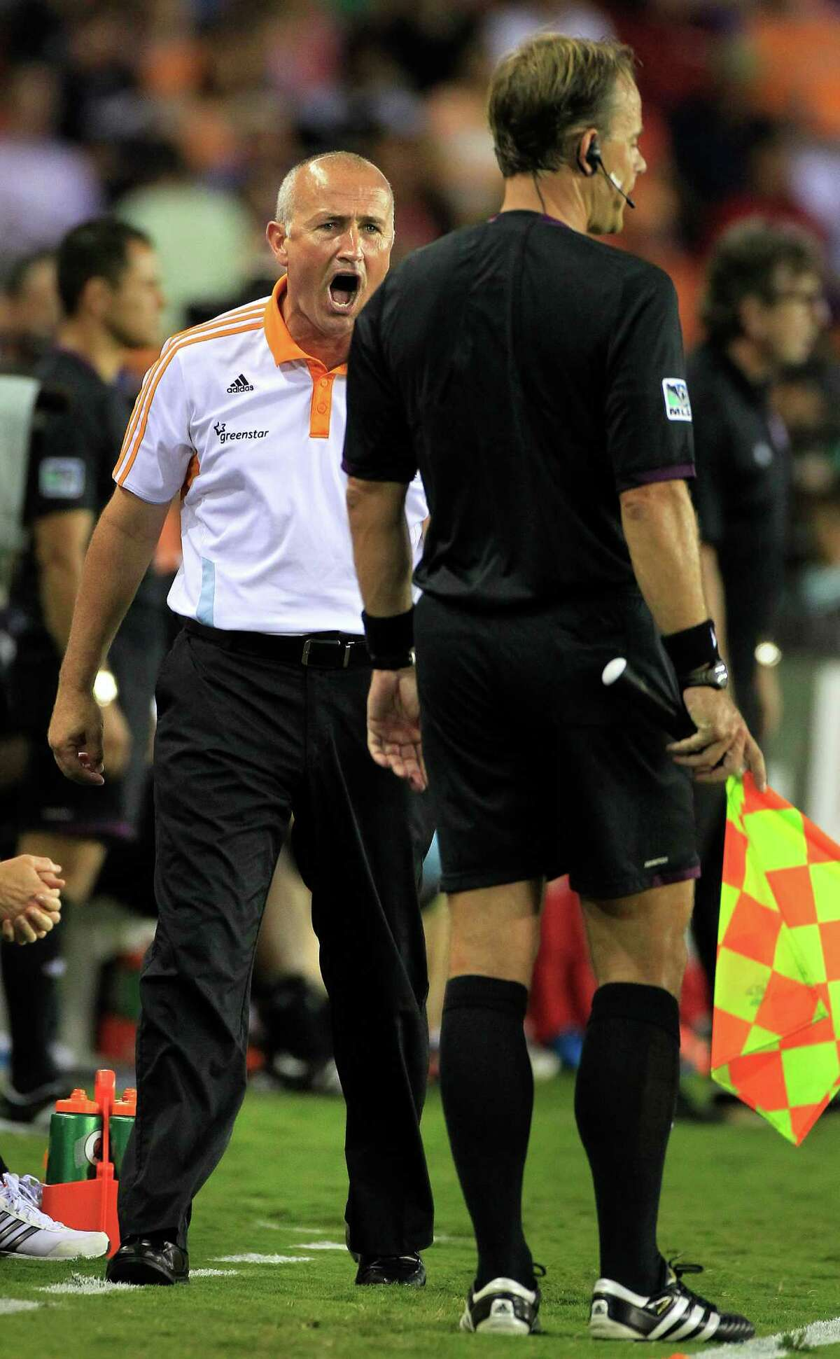 Houston Dynamo head coach Dominic Kinnear, left, yells at a referee during the second half of a soccer game against Toronto FC at BBVA Compass Stadium Wednesday, June 20, 2012, in Houston. The game ended in a 3-3 draw.