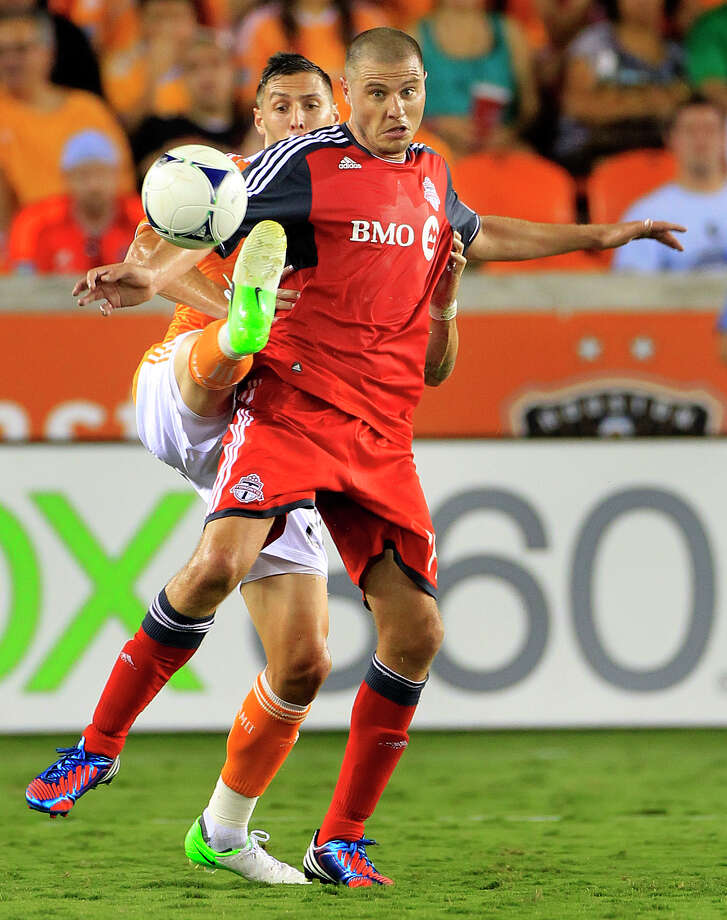 Houston Dynamo's Geoff Cameron, left, is caught up with Toronto FC's Danny Koevermans, right, as he fights for possession of the ball during the second half of a soccer game against the Houston Dynamo at BBVA Compass Stadium Wednesday, June 20, 2012, in Houston. The game ended in a 3-3 draw. Photo: Cody Duty, Houston Chronicle / © 2011 Houston Chronicle