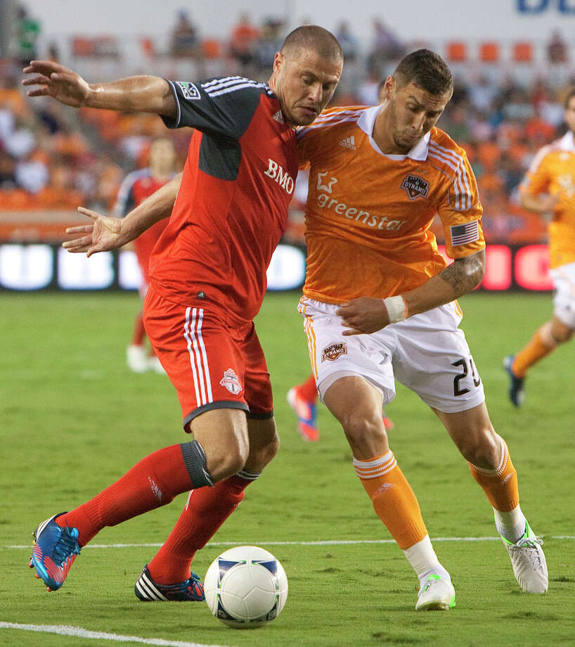 Toronto FC's Danny Koevermans, left, collides with Houston Dynamo's Geoff Cameron, right, as he fights for possession of the ball during the first half of a soccer game at BBVA Compass Stadium Wednesday, June 20, 2012, in Houston. The game ended in a 3-3 draw. Photo: Cody Duty, Houston Chronicle / © 2011 Houston Chronicle
