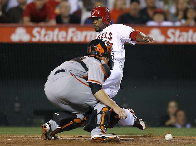Los Angeles Angels' Howard Kendrick, rear, scores past San Francisco Giants catcher Buster Posey on a hit by Erick Aybar during the fifth inning of a baseball game in Anaheim, Calif., Wednesday, June 20, 2012. (AP Photo/Chris Carlson) Photo: Chris Carlson, Associated Press