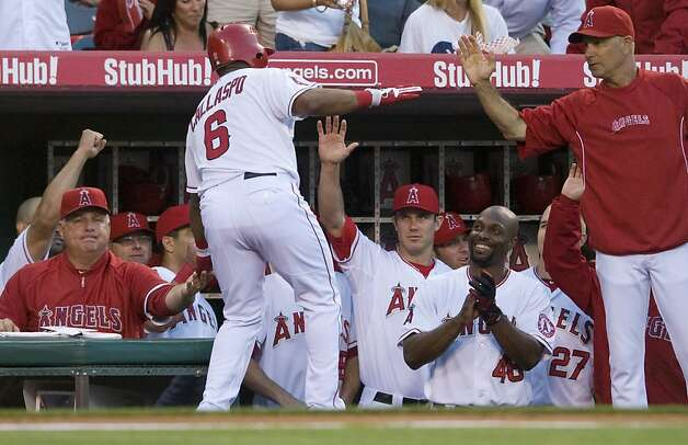 Los Angeles Angels third baseman Alberto Callaspo (6) is greeted at the dugout by coaches and teammates after hitting a solo home run in the 2nd inning Wednesday, June 20, 2012, at Angel Stadium in Anaheim, California. (Michael Goulding/Orange County Register/MCT) Photo: Michael Goulding,, McClatchy-Tribune News Service