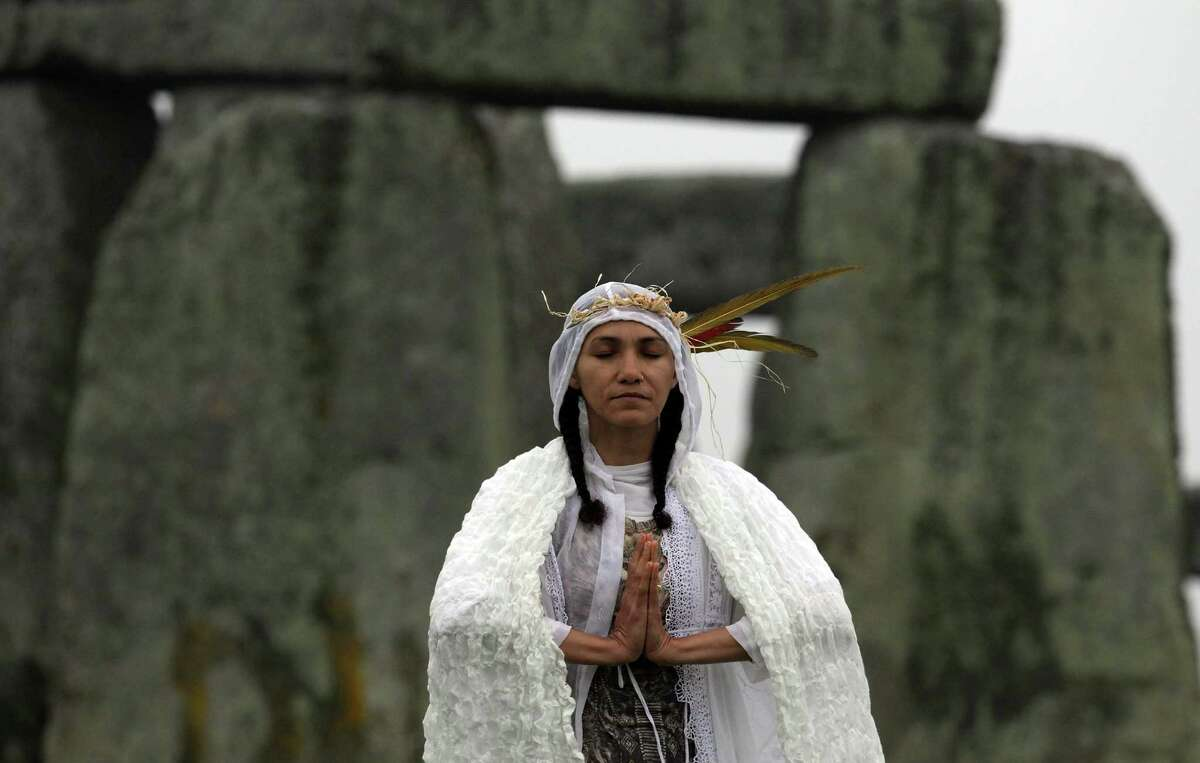 When what looks to be a high priestess has to wear a hoodie to great the summer sunrise, you know you must be in England -- or Seattle. Gleu Sunpooja stands in front of Stonehenge as solstice revelers celebrate the arrival of the midsummer sunrise at the megalithic monument.