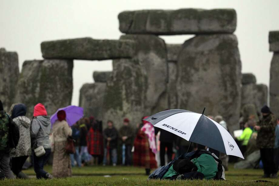 The modern-day Druids and pagans got down and got wet to greet the first summer sunrise on Thursday in Salisbury, England. They gathered around 5,000-year-old Stonehenge. And they brought their umbrellas, ponchos and assorted rain hats. Photo: Matt Cardy, Getty Images / 2012 Getty Images