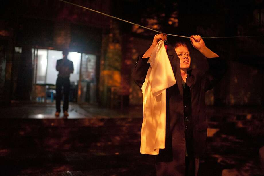 Wang Haichun, 30, takes clean laundry from a clothesline outside the parlour while Li Jian indulges in a cigarette after their supper. The three men live where they work, as their homes are situated in provinces far away from Chongqing. They live separated from their families and call home everyday to talk to them. Photo: Yue Wu, The Chronicle