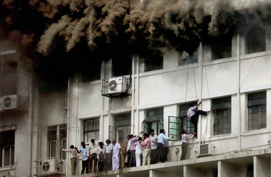 Indian employees are evacuated as smoke billows after the Maharashtra state government caught fire in Mumbai, India, Thursday, June 21, 2012. Hundreds of employees were evacuated Thursday from the seven-story government building as more than two dozen fire engines battled the major fire that raged for more than three hours in India's financial and entertainment capital. (AP Photo) Photo: Associated Press / AP