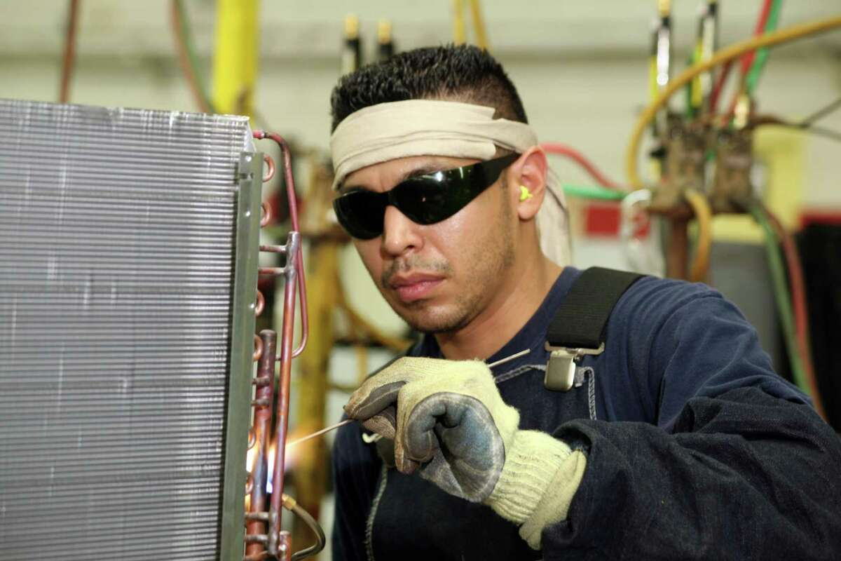 On the assembly line, Fabian Alverez brazes the refrigerant tubing on an air conditioner s condenser coil. Goodman Global was named to the Chronicle 100 top private companies list.