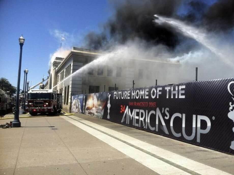 Firefighters battle a fire at the Pier 29 building, part of a construction site for next year's America's Cup, in San Francisco, California, U.S., on Wednesday, June 20, 2012. The unoccupied pier building on the Embarcadero waterfront was engulfed in a four-alarm fire, as more than 100 firefighters battled the blaze.  (Marc Perrier / Bloomberg)