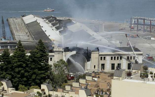 "Firefighters with the San Francisco Fire Department battle a fire at Pier 29 on the waterfront in San Francisco, Wednesday, June 20, 2012. Fire Department spokeswoman Mindy Talmadge says more than 100 firefighters are trying to ""surround the fire and drown it out."" Talmadge says no injuries have been reported.  (Jeff Chiu / Associated Press)"