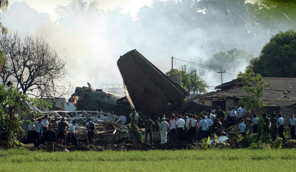 Indonesian military personnel investigate the site where an Indonesia air force plane crashed in Jakarta, Indonesia, Thursday. The Fokker F-27 turboprop plane crashed into homes in the capital Thursday during a routine training flight, killing at least 10 people.