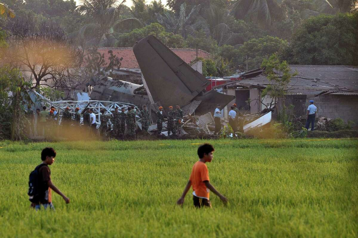 Youths walk on a rice field as the site where an Indonesian air force plane crashed is seen in the background in Jakarta, Indonesia, Thursday. The Fokker F-27 turboprop plane slammed into homes and ignited a fireball in the crowded capital while trying to land Thursday, killing at least 10 people, a military official said.