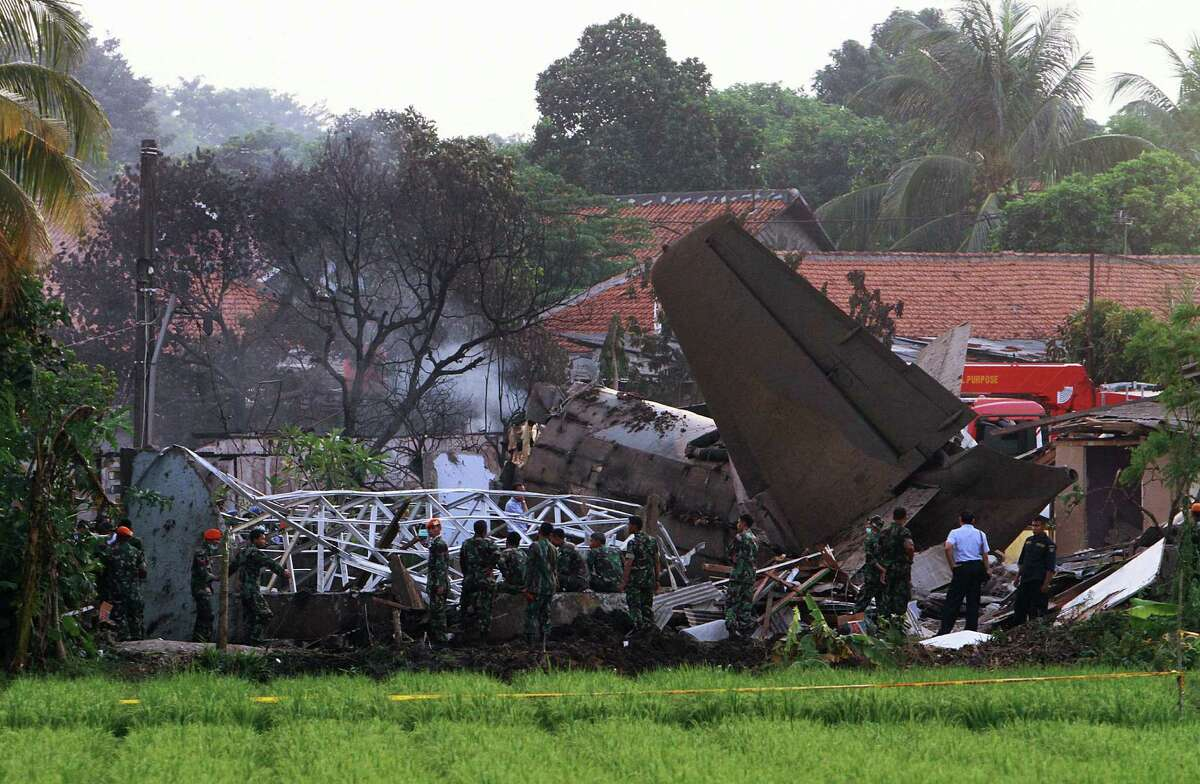 Emergency personnel look through the rubble after an Indonesian military aircraft crashed in Jakarta on Thursday. The Fokker-27 crashed into a military housing complex in the capital Jakarta, killing at least 10 people. ( ANDRA BIMO/AFP/GettyImages)