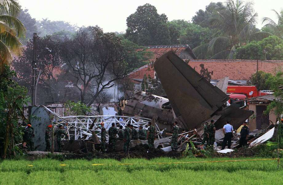 Emergency personnel look through the rubble after an Indonesian military aircraft crashed in Jakarta on Thursday. The Fokker-27 crashed into a military housing complex in the capital Jakarta, killing at least 10 people.        ( ANDRA BIMO/AFP/GettyImages) Photo: AFP, AFP/Getty Images / 2012 AFP
