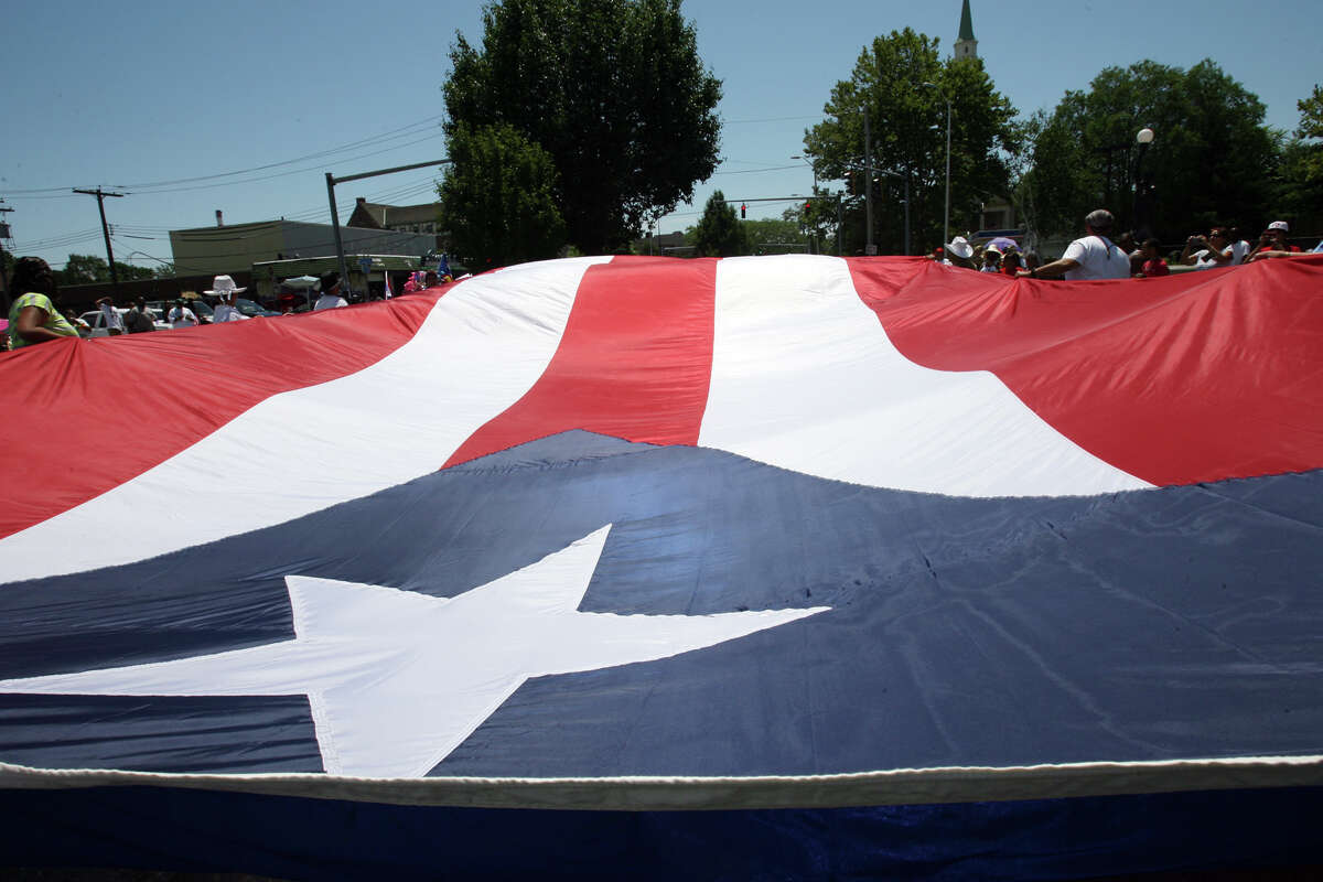Habitat for Humanity Youth United carry a large flag in the 18th annual Puerto Rican Day Parade in Bridgeport on Sunday, July 10, 2011.