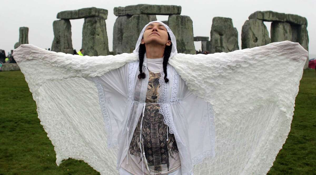 SALISBURY, ENGLAND - JUNE 21: Gleu Sunpooja stands in front of Stonehenge as solstice revellers celebrate the arrival of the midsummer sunrise at the megalithic monument on June 21, 2012 near Salisbury, England. Cloudy skies and a Met Office weather warning for heavy rain meant the numbers of revellers who annually gather at the 5,000 year old stone circle to see the sunrise on the Summer Solstice was down on previous years. The solstice sunrise marks the longest day of the year in the Northern Hemisphere.