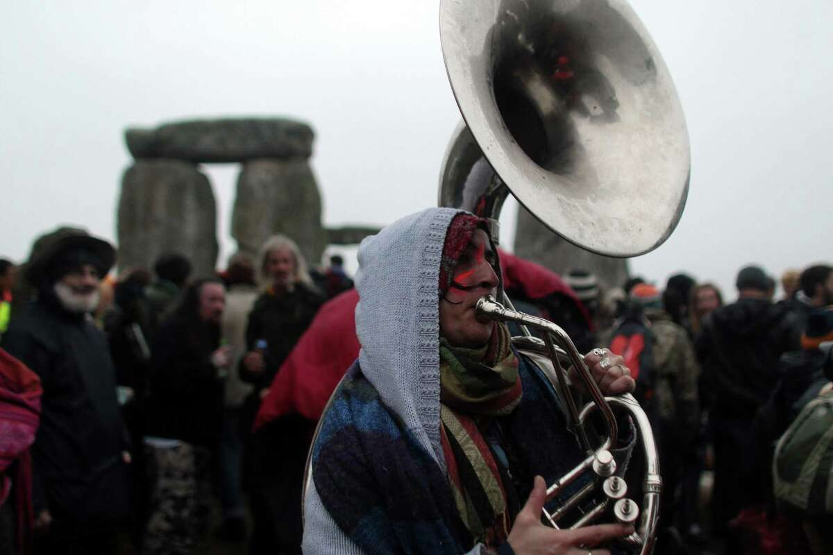 SALISBURY, ENGLAND - JUNE 21: Solstice revellers celebrate the arrival of the midsummer dawn at the megalithic monument of Stonehenge on June 21, 2012 near Salisbury, England. Cloudy skies and a Met Office weather warning for heavy rain meant the numbers of revellers who annually gather at the 5,000 year old stone circle to see the sunrise on the Summer Solstice was down on previous years. The solstice sunrise marks the longest day of the year in the Northern Hemisphere.