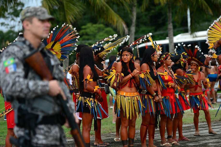 "A Brazilian military policeman stands guard next to Brazilian natives, upon their arrival at RioCentro to hand out the Kari-Oca II Declaration to leaders attending the UN Conference on Sustainable Development, Rio+20, in Rio de Janeiro, Brazil, on June 21, 2012. World leaders attending the UN summit in Rio weighed steps to root out poverty and protect the environment as thousands of activists held several protests to denounce Amazon rainforest deforestation, the plight of indigenous peoples and the ""green economy"" being advocated at the UN gathering.  AFP PHOTO / CHRISTOPHE SIMONCHRISTOPHE SIMON/AFP/GettyImages Photo: Christophe Simon, AFP/Getty Images"