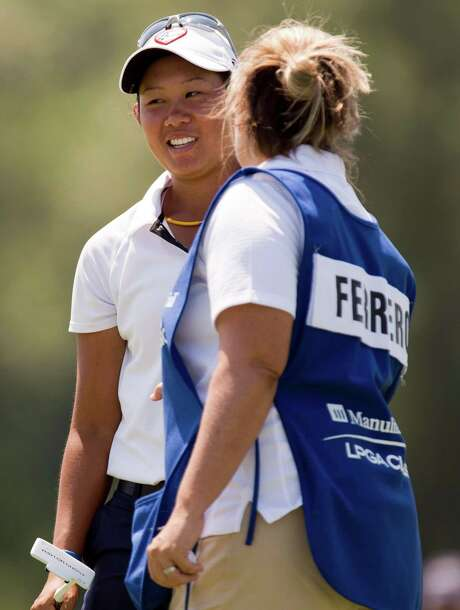 Sandra Changkija, left, smiles as she is congratulated by Lisa Ferrero's caddie after making a birdie putt from the fringe on the eighth green during the first round of the LPGA Classic golf tournament in Waterloo, Ontario on Thursday June 21, 2012. Photo: AP