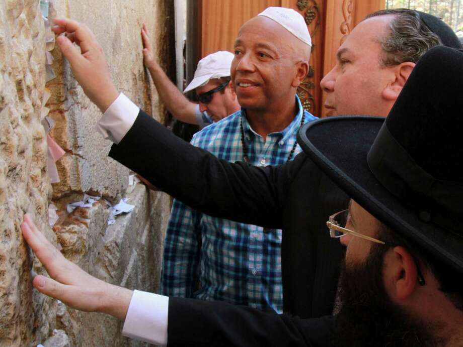 Hip hop mogul Russell Simmons, second left, looks on as US Rabbi Marc Schneier president and founder of the Foundation for Ethnic Understanding (FFEU), second right, and the Western Wall rabbi, Shmuel Rabinovich, right, touch stones of the Western Wall, the holiest site where Jews can pray, in Jerusalem's Old City, Thursday, June 21, 2012. The cofounder of the pioneering Def Jam Recordings record label, which has represented such artists like the Beastie Boys, Jay-Z, Lady Gaga, Jennifer Lopez, LL Cool J and Kanye West, is in Israel on the invitation of Israeli President Shimon Peres.(AP Photo/Blake Sobczak) Photo: Blake Sobczak