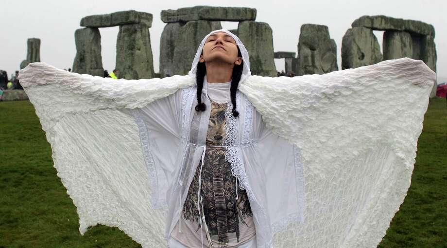 Gleu Sunpooja stands in front of Stonehenge as solstice revellers celebrate the arrival of the midsummer sunrise at the megalithic monument on June 21, 2012 near Salisbury, England. Cloudy skies and a Met Office weather warning for heavy rain meant the numbers of revellers who annually gather at the 5,000 year old stone circle to see the sunrise on the Summer Solstice was down on previous years. The solstice sunrise marks the longest day of the year in the Northern Hemisphere.  (Photo by Matt Cardy/Getty Images)  *** BESTPIX *** Photo: Matt Cardy, Getty Images / 2012 Getty Images
