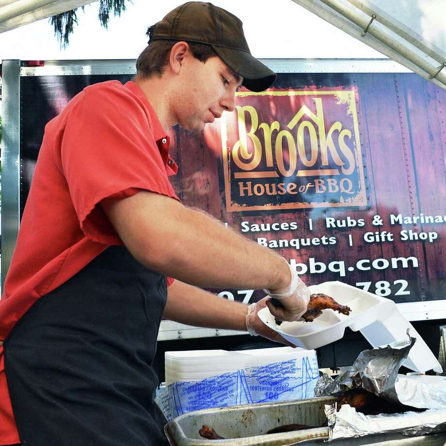 Perry Felter of Brooks House of BBQ in Oneonta smakes up barbecued chicken dinners at the Rotterdam United Methodist Church in Rotterdam Saturday June 16, 2012.   (John Carl D'Annibale / Times Union) Photo: John Carl D'Annibale / 00018102A