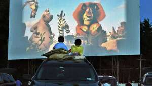 Brothers Andrew, 9, left, and Stephen Gower, 11, of Selkirk watch a movie from atop the family car at the Jericho Drive-In in Glenmont Saturday June 16, 2012.   (John Carl D'Annibale / Times Union)
