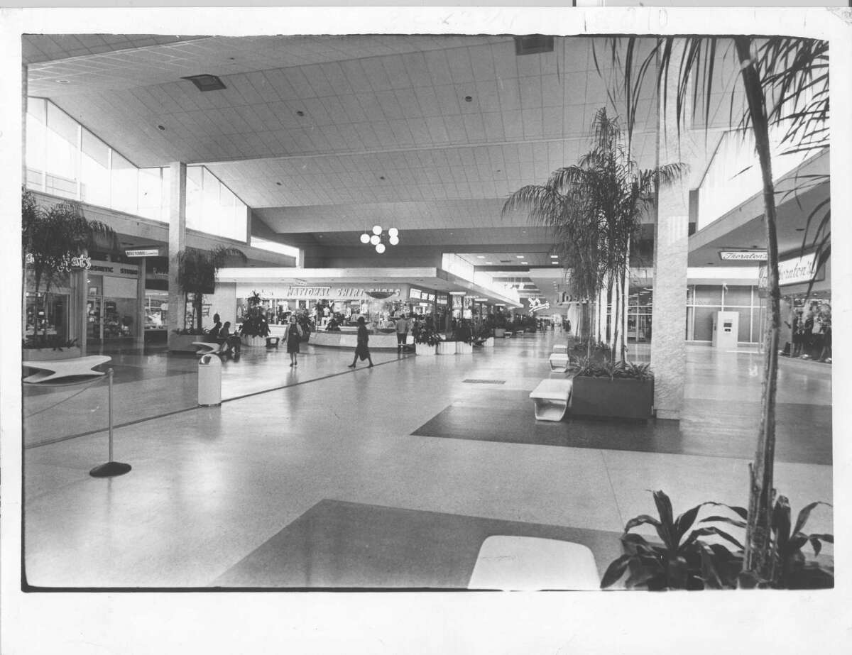 """Original Chronicle caption, March 5, 1965: """"KEEPING OUT THE ELEMENTS. Workmen are putting finishing touches to the $1 million project in which Gulfgate Shopping City covered,, enclosed and air-conditioned its 81,000-square-foot mall. All 72 stores in the Southwest's largest shopping center now open off the mall as illustrated in this shot by Chronicle photographer Tom Colburn."""""""