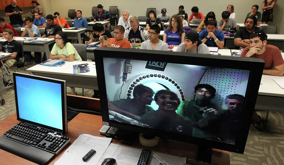 Students video conference with aquanauts of the NASA Extreme Environment Mission Operations (NEEMO) project at San Antonio College (SAC) on Thursday, June 21, 2012. Students from SAC's Early Development of General Engineering (EDGE) program asked questions of the aquanauts who are living in an underwater habitat off the southeast coast of Florida. NEEMO attempts to simulate the environments of deep space exploration. The goal of EDGE is to aid students in the development of interest in the field of engineering. The aquanauts are: Timothy Peake (from left), Dottie Metcalf-Lindenburger, Kimiya Yui and Steven Squyres. The video conferece lasted about 30 minutes. Photo: Kin Man Hui, San Antonio Express-News / @2012 San Antonio Express-News