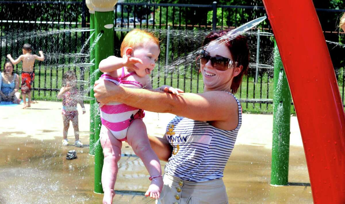 Margaret Connors, 10 months-old, gets cool drink as her mom, Priscilla holds her at the Rogers Park spray park in Danbury Thursday, June 22, 2012.