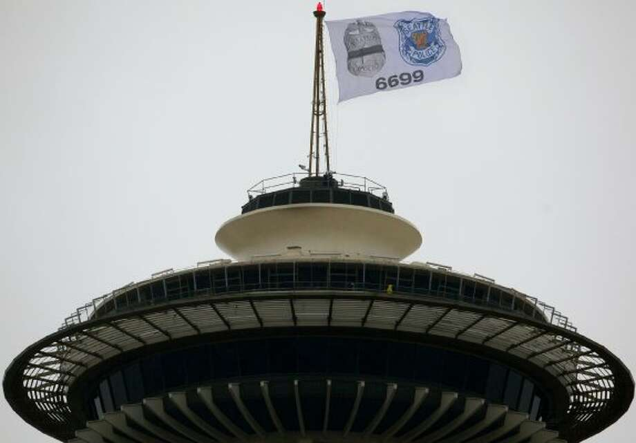 A flag flies atop Seattle's Space Needle on Nov. 5, 2009 honoring Officer Timothy Brenton who was killed on Halloween while he sat in his patrol car with an officer who was undergoing training. (Joshua Trujillo, Seattlepi.com) (Joshua Trujillo)