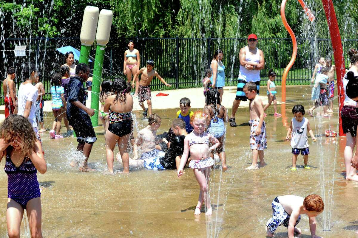The Rogers Park spray park is a good place for area residents, including Trica Connors, 4, right center, to keep cool in Danbury Thursday, June 22, 2012.