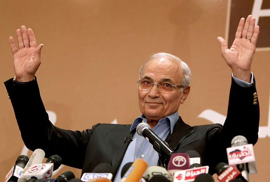 "Egypt's presidential candidate Ahmed Shafiq, the last premier of ousted Egyptian strongman Hosni Mubarak, salutes his supporters during a press conference in Cairo, on June 21, 2012.  Egypt on Thursday braced for a showdown between the military and the Muslim Brotherhood as the electoral commission delayed announcing the winner of a presidential poll claimed by the Islamists. A delay in announcing the results from the run-off, which had been due on Thursday, heightened fears of a ""soft coup"" by the ruling military, which has already disbanded the Islamist-led parliament and granted itself sweeping powers.  AFP PHOTO/MARWAN NAAMANIMARWAN NAAMANI/AFP/GettyImages Photo: Marwan Naamani, AFP/Getty Images"