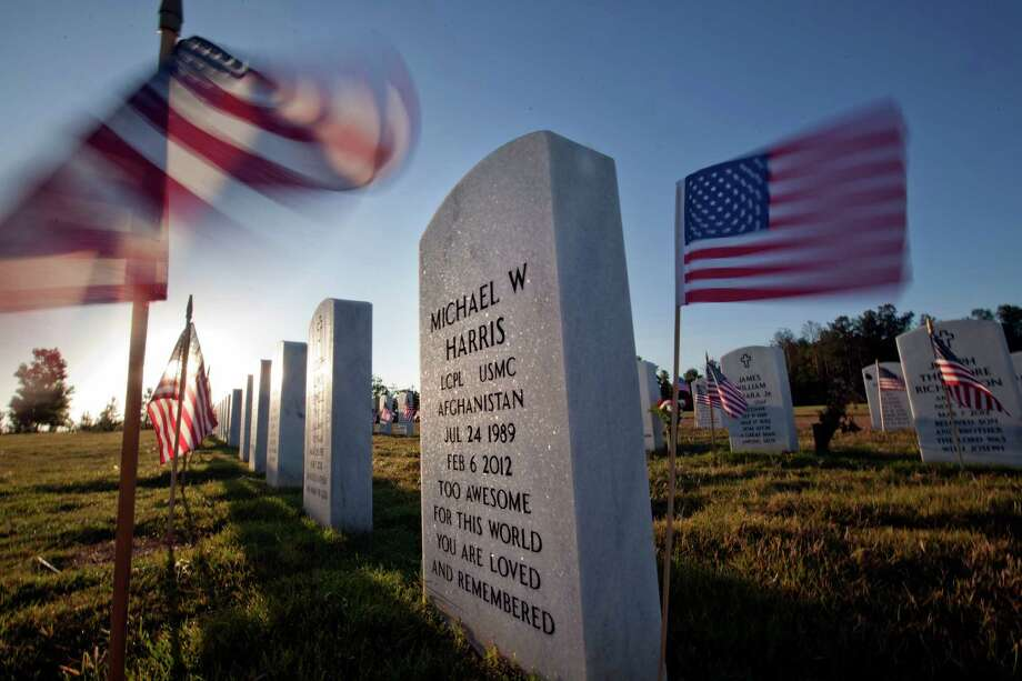 American flags wave near the grave of Marine Lance Cpl. Michael Harris as the the sun rises over Georgia National Cemetery on Memorial Day, Monday, May 28, 2012, in Canton, Ga. Harris died Feb. 6, 2012, in North Carolina. Photo: AP