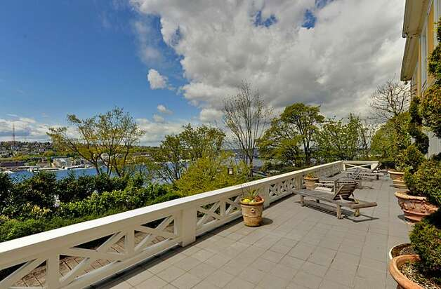 Deck, looking over Lake Union, of 1117 Boylston Ave E. The 9,020-square-foot house, built in 1910, has six bedrooms and 6.5 bathrooms, including a master bedroom with a fireplace and a nanny's quarters, a wood-paneled library with a fireplace and a sunroom with French doors leading to the deck. The property is about an acre, with a fountain, gazebo, tennis court and three-car garage. It's listed for $3.199 million. Photo: Jason Mercio/Mercio Photography, Courtesy Nancy Williams/Windermere Real Estate