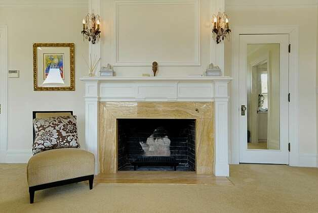 Master bedroom fireplace of 1117 Boylston Ave E. The 9,020-square-foot house, built in 1910, has six bedrooms and 6.5 bathrooms, including a nanny's quarters, a wood-paneled library with a fireplace and a sunroom with French doors leading to a huge deck looking down on Lake Union. The property is about an acre, with a fountain, gazebo, tennis court and three-car garage. It's listed for $3.199 million. Photo: Jason Mercio/Mercio Photography, Courtesy Nancy Williams/Windermere Real Estate