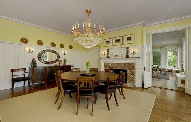 Dining room of 1117 Boylston Ave E. The 9,020-square-foot house, built in 1910, has six bedrooms and 6.5 bathrooms, including a master bedroom with a fireplace and a nanny's quarters, a wood-paneled library with a fireplace and a sunroom with French doors leading to a huge deck looking down on Lake Union. The property is about an acre, with a fountain, gazebo, tennis court and three-car garage. It's listed for $3.199 million. Photo: Jason Mercio/Mercio Photography, Courtesy Nancy Williams/Windermere Real Estate