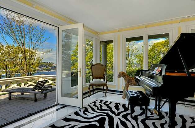 Sunroom, with French doors leading to deck, of 1117 Boylston Ave E. The 9,020-square-foot house, built in 1910, has six bedrooms and 6.5 bathrooms, including a master bedroom with a fireplace and a nanny's quarters and a wood-paneled library with a fireplace. The property is about an acre, with a fountain, gazebo, tennis court and three-car garage. It's listed for $3.199 million. Photo: Jason Mercio/Mercio Photography, Courtesy Nancy Williams/Windermere Real Estate