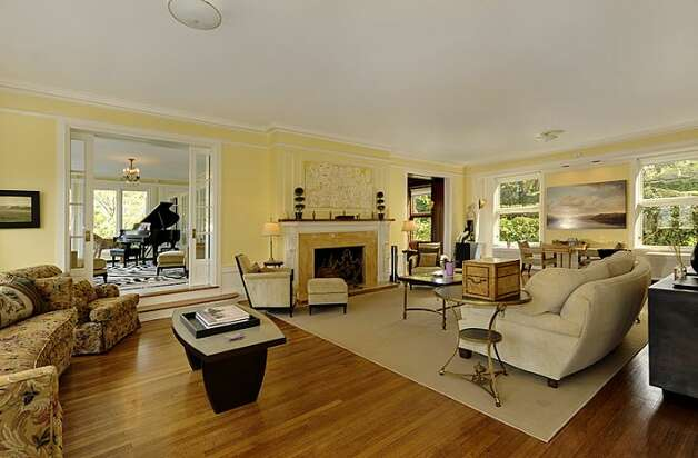 Living room of 1117 Boylston Ave E. The 9,020-square-foot house, built in 1910, has six bedrooms and 6.5 bathrooms, including a master bedroom with a fireplace and a nanny's quarters, a wood-paneled library with a fireplace and a sunroom with French doors leading to a huge deck looking down on Lake Union. The property is about an acre, with a fountain, gazebo, tennis court and three-car garage. It's listed for $3.199 million. Photo: Jason Mercio/Mercio Photography, Courtesy Nancy Williams/Windermere Real Estate