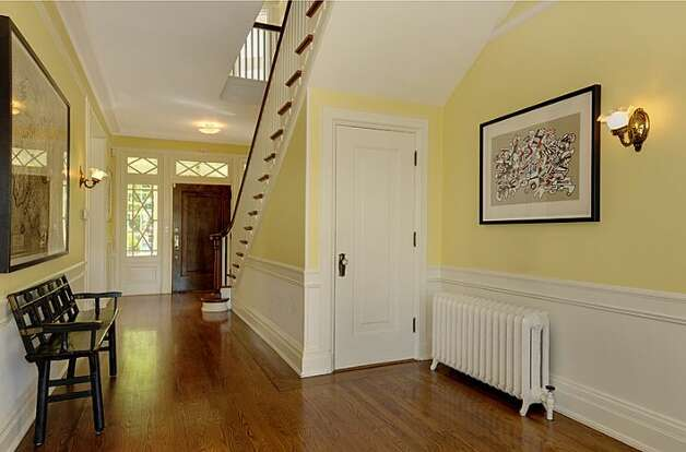 Foyer of 1117 Boylston Ave E. The 9,020-square-foot house, built in 1910, has six bedrooms and 6.5 bathrooms, including a master bedroom with a fireplace and a nanny's quarters, a wood-paneled library with a fireplace and a sunroom with French doors leading to a huge deck looking down on Lake Union. The property is about an acre, with a fountain, gazebo, tennis court and three-car garage. It's listed for $3.199 million. Photo: Jason Mercio/Mercio Photography, Courtesy Nancy Williams/Windermere Real Estate
