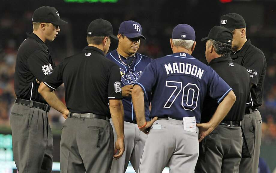 Umpires Cory Blaser, left, Chris Guccione, Tim Tschida, second from right, and Jeff Nelson, right, talk with Tampa Bay Rays relief pitcher Joel Peralta, and manager Joe Maddon (70) as they eject Peralta during the eighth inning of the Rays' baseball game against the Washington Nationals on Tuesday, June 19, 2012, in Washington. Peralta was ejected in the eighth inning for having a foreign substance on his glove. (AP Photo/Alex Brandon) Photo: Alex Brandon, Associated Press
