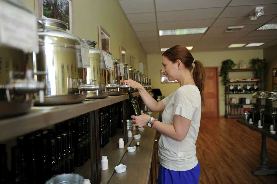 Alina Lawrence, the owner of the shop Olivette in Darien, which sells 48 varieties of olive oils and balsamic vinegars draws some of the olive oils Wednesday, June 20, 2012. Photo: Helen Neafsey / Greenwich Time