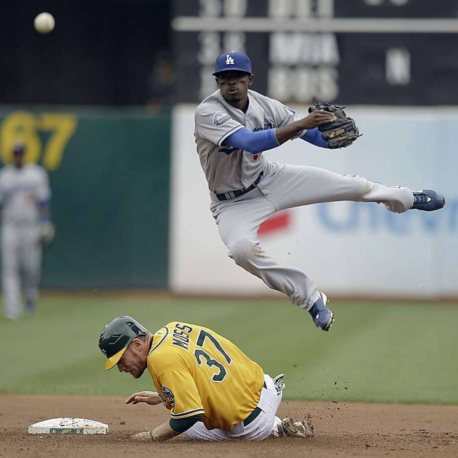 Los Angeles Dodgers shortstop Dee Gordon hops over Oakland Athletics' Brandon Moss (37) as he completes a double play throw to first base during the second inning of a baseball game Thursday, June 21, 2012, in Oakland, Calif. The A's Derek Norris was out at first base on the play. (AP Photo/Ben Margot) Photo: Ben Margot, Associated Press