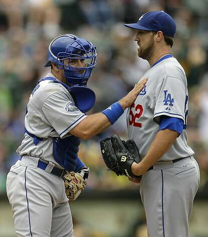 Los Angeles Dodgers catcher Matt Treanor, left, comes to the pitching mound to talk with pitcher Josh Lindblom (52) in the ninth inning of a baseball game against the Oakland Athletics, Thursday, June 21, 2012, in Oakland, Calif. (AP Photo/Ben Margot) Photo: Ben Margot, Associated Press