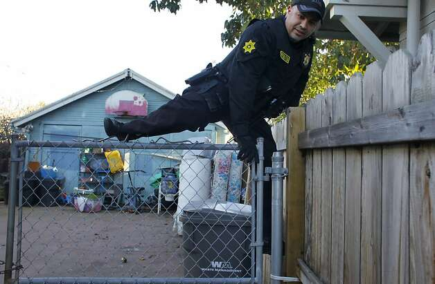 Ray Mizyed of the County Sheriffs Probation Department climbs up and around a fence where a number of barking dogs guarded premises, in search for guns that were thrown by suspects during a foot chase down Auseon Ave, Wednesday February 15, 2012, in East Oakland, Calif. Mitzyed is working with the Oakland Police Department as part of the 100 block initiative which was created by Mayor Jean Quan to reduce the violence in the areas  where 90 percent of the city's homicides and shootings allegedly occur. Photo: Lacy Atkins, The Chronicle