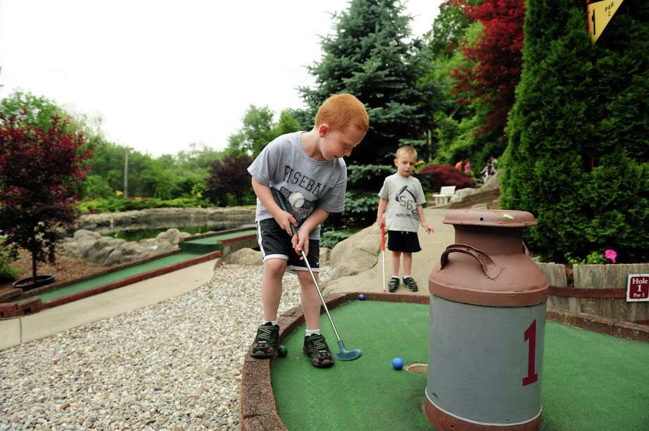 Six-year-old John Douglass, of Seymour, putts on the first hole at Olde Sawmill Grill and Miniature Golf Course in Oxford, Conn. as younger brother Sean, 3, looks on Tuesday, June 19, 2012. Photo: Autumn Driscoll / Connecticut Post