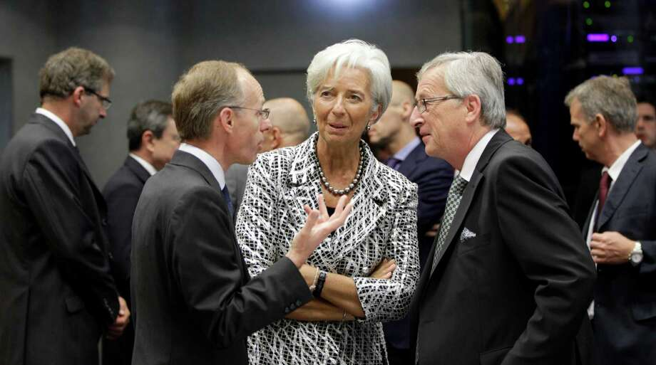 Managing Director of the International Monetary Fund Christine Lagarde, center, speaks with Luxembourg's Prime Minister and President of the eurogroup Jean-Claude Juncker, right, and Luxembourg's Economy Minister Luc Freiden during a meeting of eurozone finance ministers in Luxembourg on Thursday, June 21, 2012. As the cracks in the euro currency seem to grow even wider, finance ministers from the 17 countries that use the currency brainstorm Thursday on how to stabilize it. (AP Photo/Virginia Mayo) Photo: Virginia Mayo