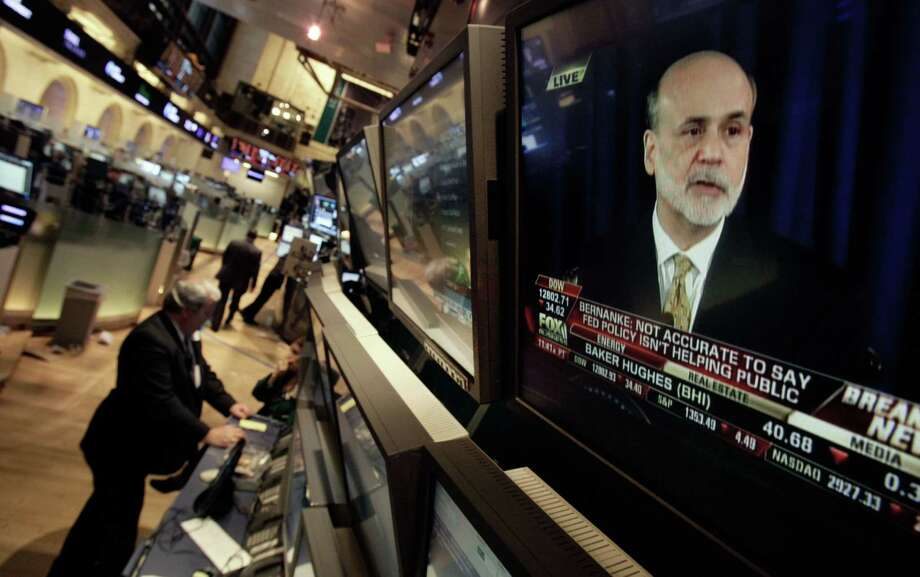 FILE - In this Wednesday, June 20, 2012, file photo, Federal Reserve chairman Ben Bernanke is visible on a television monitor on the floor of the New York Stock Exchange. Futures augured a weak start Thursday June 21, 2012 on Wall Street with Dow futures nearly unchanged at 12,765. S&P 500 futures dropped 0.5 percent to 1,343.50.  (AP Photo/Richard Drew, File) Photo: Richard Drew