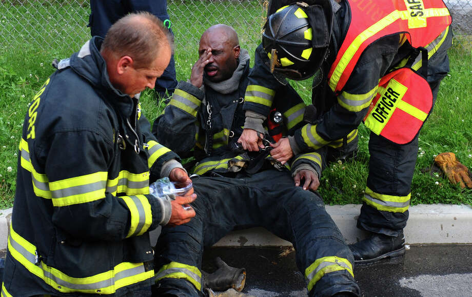 A firefighter receives medical attention, during a large warehouse fire along Railroad Street in Bridgeport, Conn. on Thuursday June 21, 2012. Photo: Christian Abraham / Connecticut Post