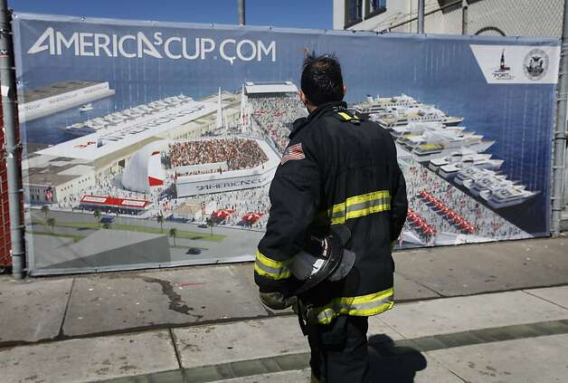A firefighter pauses to view a rendering of the America's Cup village while taking a break from fighting a four-alarm blaze that severely damaged Pier 29 in San Francisco, Calif. on Wednesday, June 20, 2012. Photo: Paul Chinn, The Chronicle