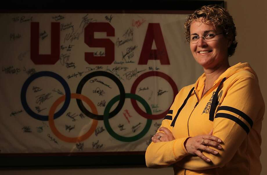 Standing with a signed Olympic flag from her work as an assistant coach for the U.S. women's swim team in 2004, Cal women's swim coach Teri McKeever has  been named head coach for the same squad in the 2012 Olympic Games in London. Photo: Mathew Sumner, Special To The Chronicle
